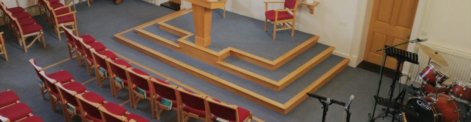 hadleigh baptist church main worship area with red chairs, drum kit, piano, music stands, microphones and lectern